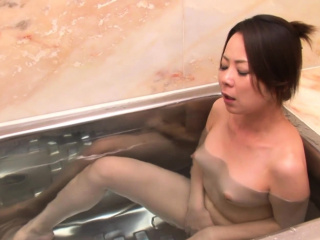 Naughty Asian girl fingers her pussy in the bathtub