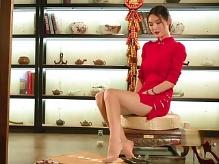Chinese girl in traditional garments play feet with honoured